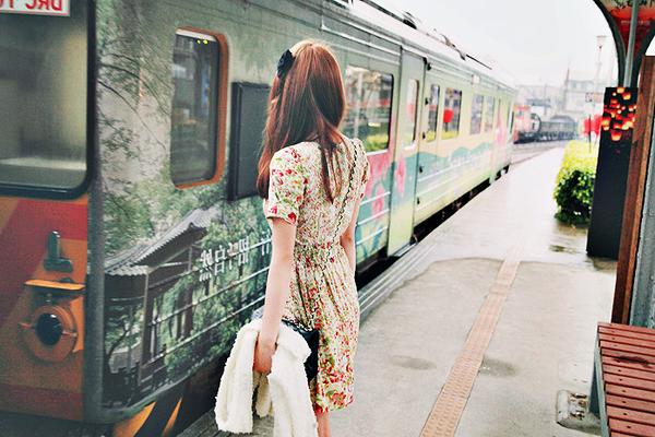 Mujer con vestido de flores esperando el transporte público