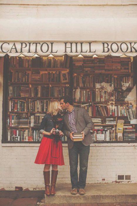 Pareja de novios besándose afuera de una tienda de libros