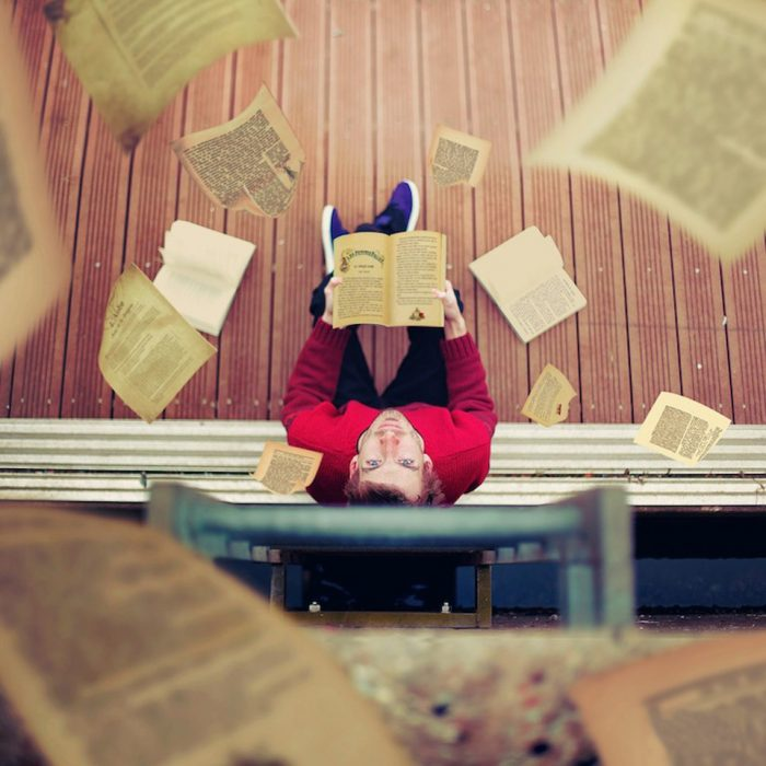 Chico vestido de rojo con un libro en las manos mirando para arriba
