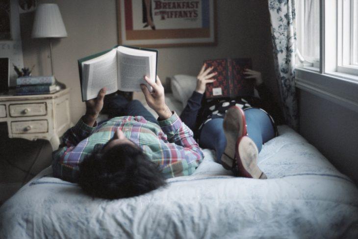 Pareja de novios en la cama leyendo un libro