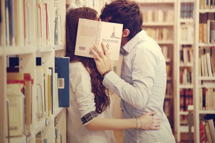 pareja de novios besándose en una biblioteca