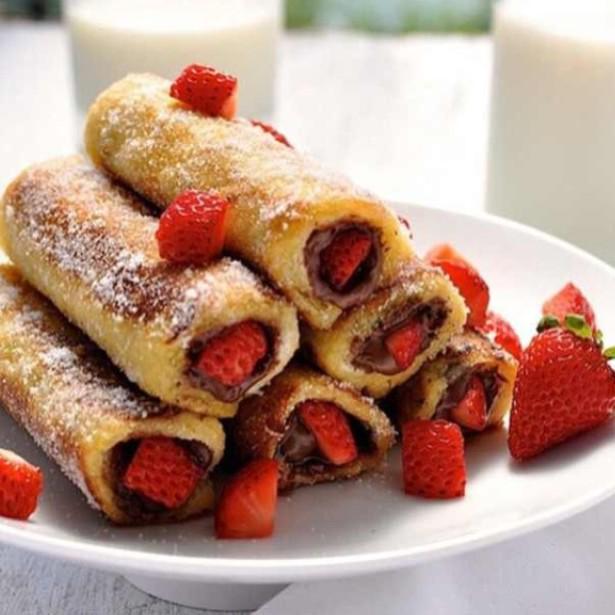 rollos de nutella con fresas sobre un plato
