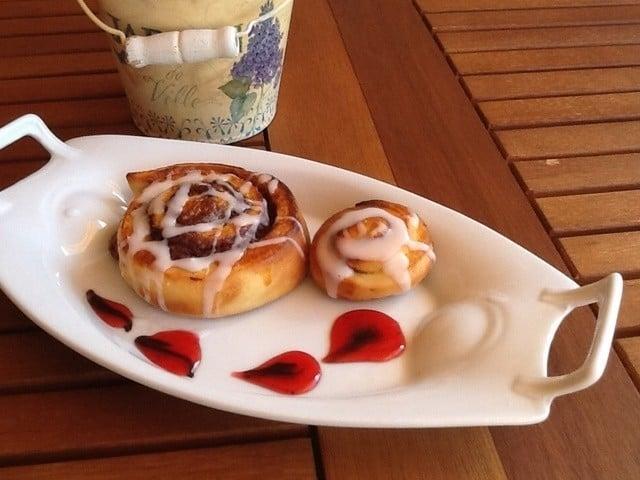 rollos glaseados con nutella servidos en un plato con jarabe de fresa y crema