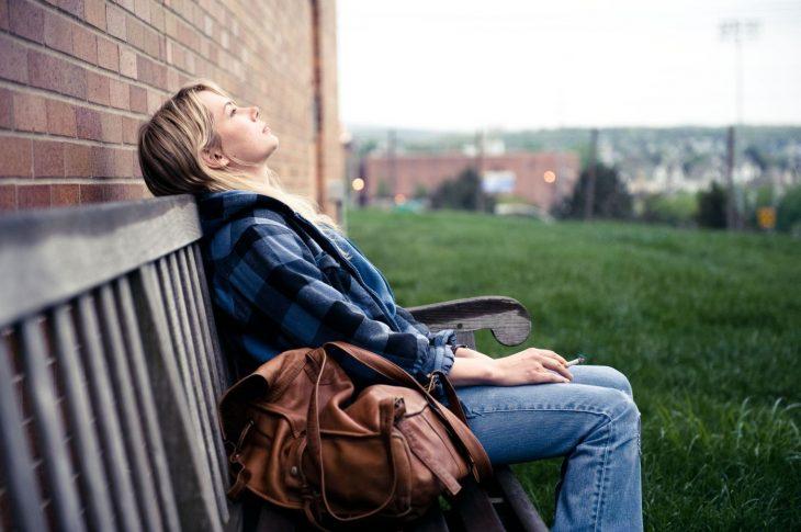escena de la película blue valentine donde la protagonista esta sentada en una banca fumando y viendo hacia le cielo