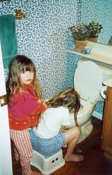 niña vomitando y otra sosteniéndole el cabello