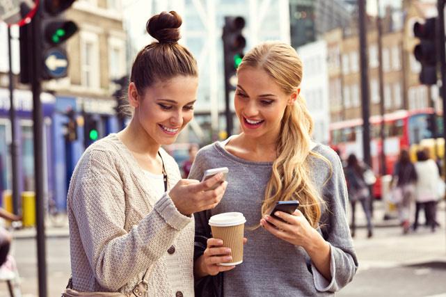 mujeres con el celular en la mano tomándose un café