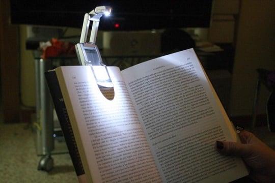 lampara que se posa en un libro para iluminarlo
