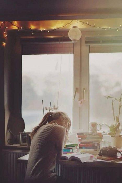 Chica leyendo un libro en la ventana
