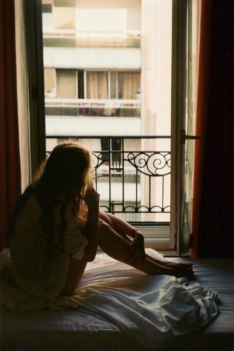 Chica observando por la ventana de su habitación