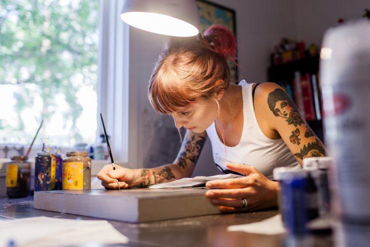 Chica con tatuajes pintando