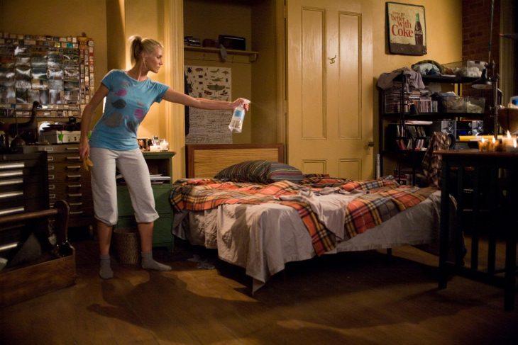 mujer rociando la cama con aromatizante