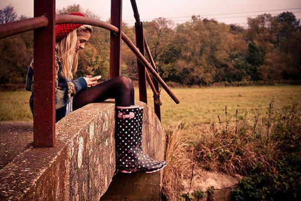 mujer sentada en un puente revisando su celular