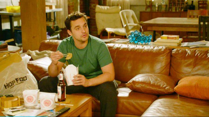hombre sentado en un sofá comiendo comida china