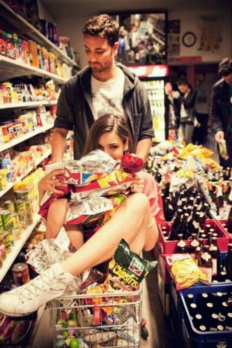 mujer y hombre con el carrito del supermercado lleno de productos