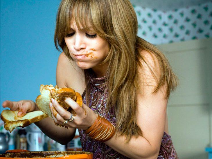 mujer comiendo con pan directo de una olla de comida
