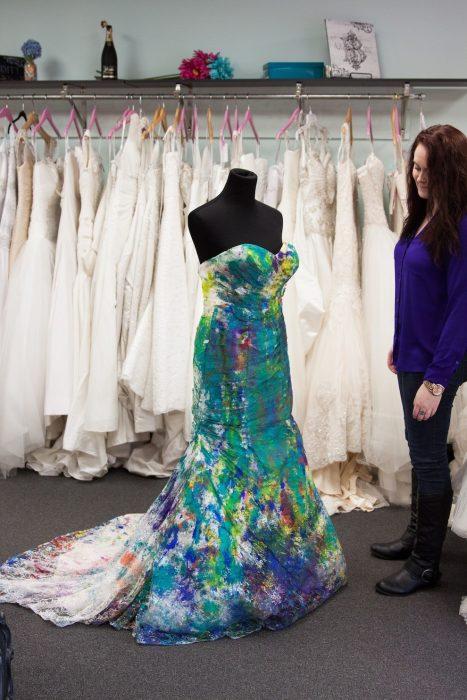 novia parada junto a su vestido de novia lleno de pintura que esta en una tienda de vestidos