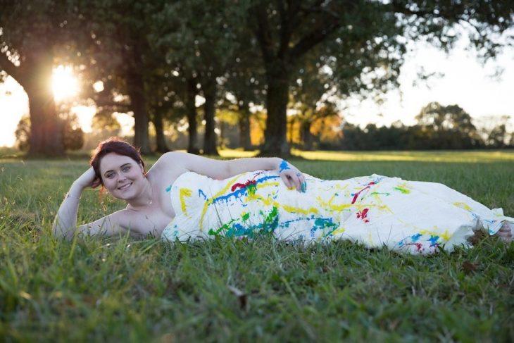 novia con su vestido lleno de pintura recostada en el pasto