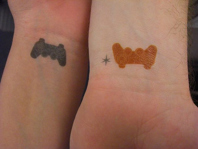 Pareja mostrando sus muñecas con tatuajes en forma de controles de video juego