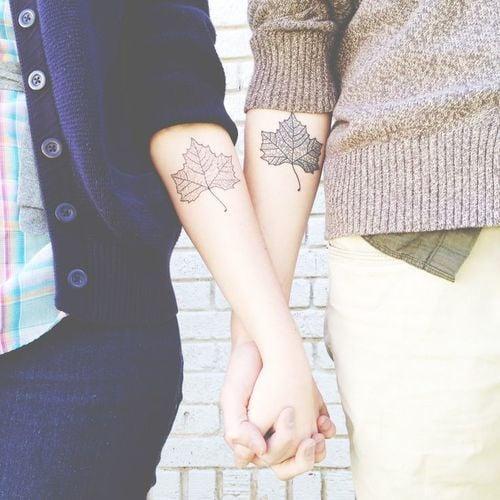 pareja mostrando sus tatuajes en los brazos en forma de una hoja de parra