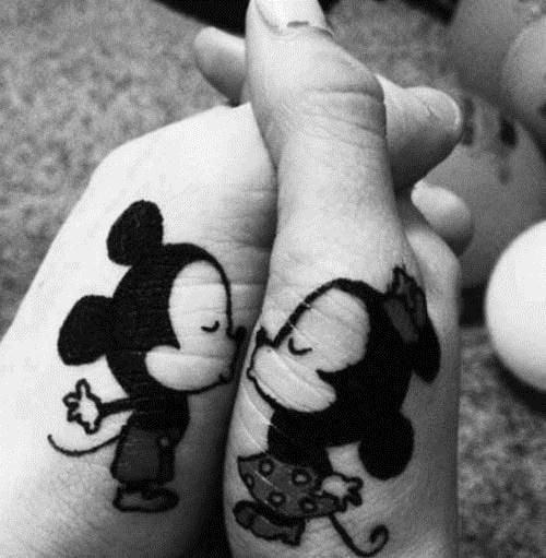 Manos entrelazadas de una pareja mostrando sus tatuajes en forma de mimi y mikey mouse