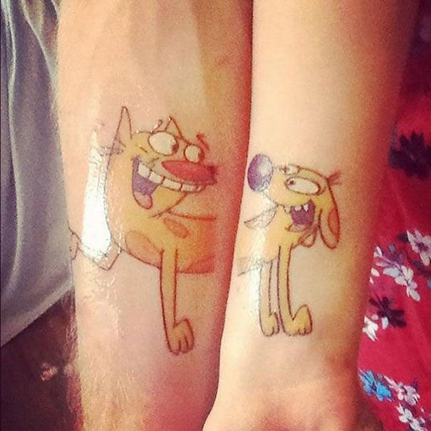 """Pareja mostrando sus brazos con tatuajes en forma de caricatura """"catdog"""""""