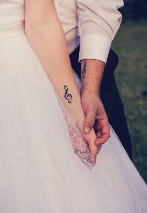 Pareja el día de su boda mostrando sus tatuajes en el brazo en forma de clave de sol