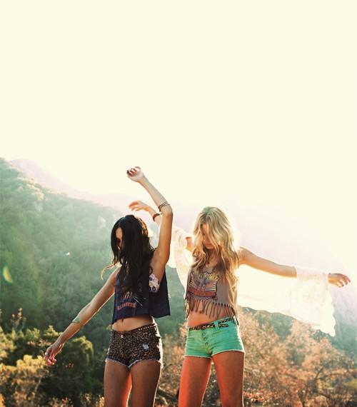 chicas sobre una roca gigante paradas bailando y extendiendo sus brazos