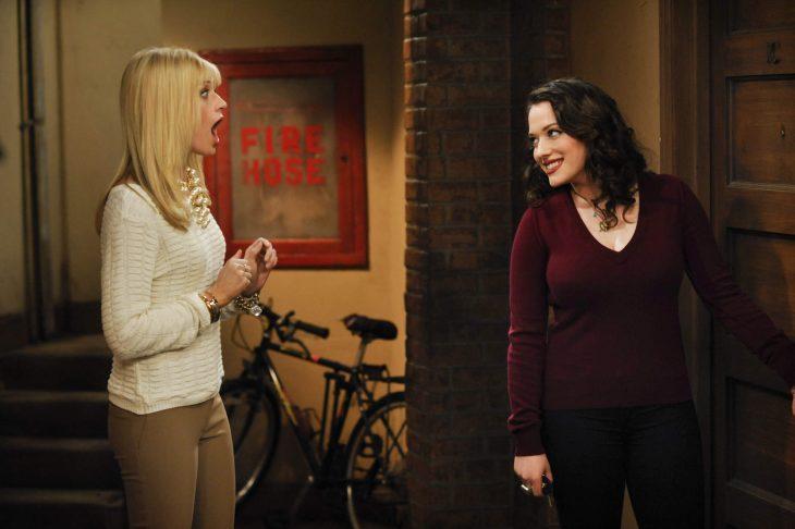 escena de la serie two broke girls la protagonista esta sorprendida tratando de abrir la puerta de su departamento
