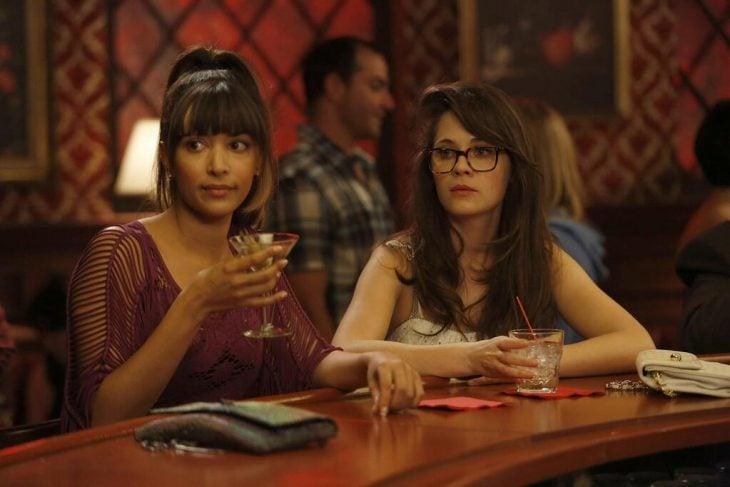 cece and jess de new girl bebiendo sentadas en la barra de un bar