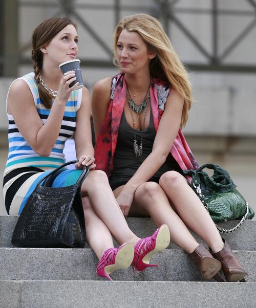escena de la serie gossip girls serena y blair sentadas en unos escalones platicando y tomando café