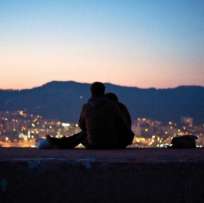 novios sentados viendo la ciudad desde un mirador