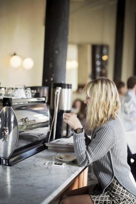 chica en una barra tomando café sola
