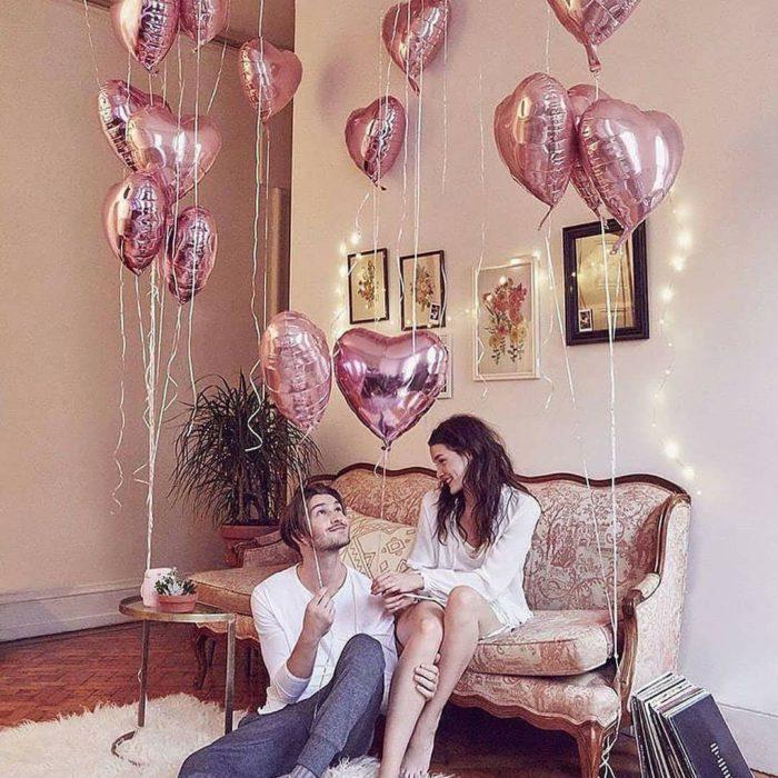 Pareja en sala de una casa con globos en forma de corazón