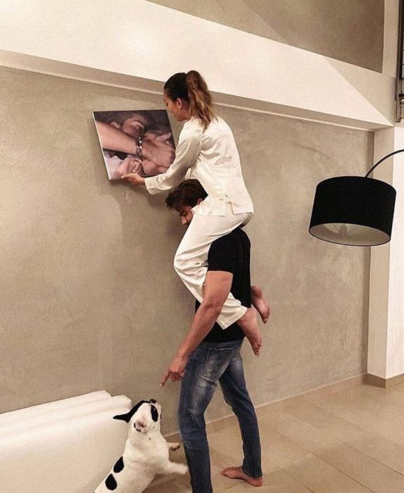 Pareja acomodando un cuadro en la pared