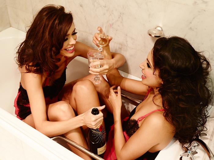Chicas en una bañera bebiendo vino