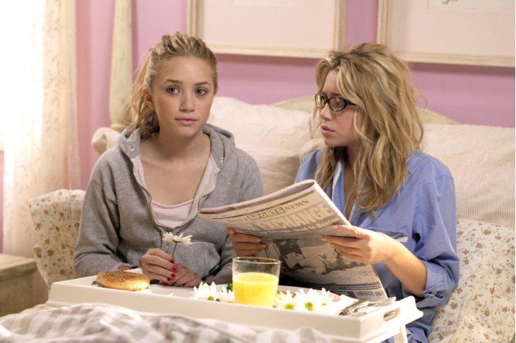 chicas recostadas en la cama comiendo y leyendo el periódico