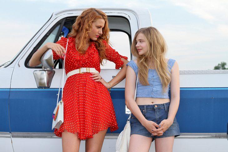 chicas recargadas en una camioneta mientras una mira a la otra