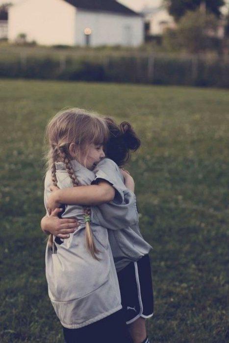 niñas abrazándose en un campo de fútbol
