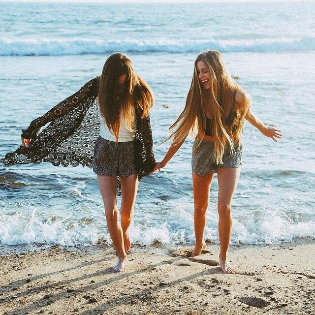 chicas tomadas de la mano caminando por la playa