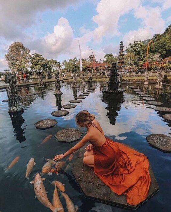 Chica frente a estanque de peces koi