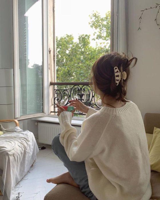 Mujer joven viendo hacia la ventana