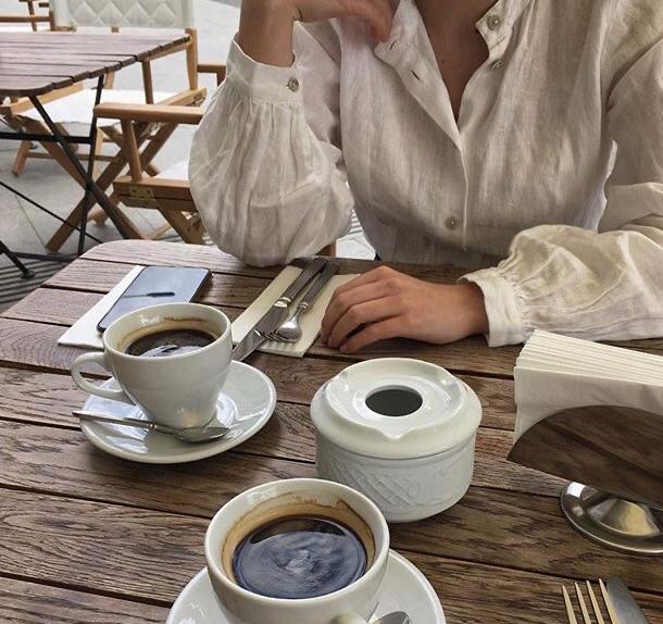Manos de una mujer sentada en una mesa frente al café