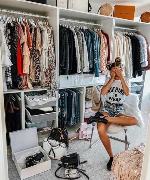 Chica frente a un closet repleto de ropa