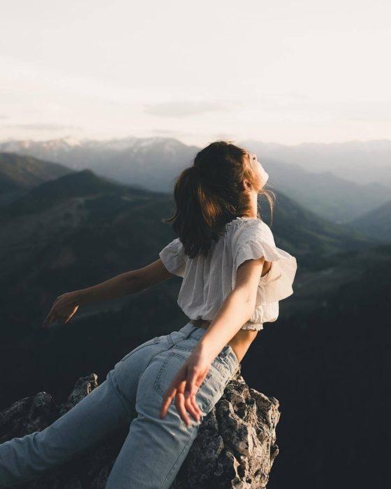 Mujer en la cima de una montaña con la cara al sol