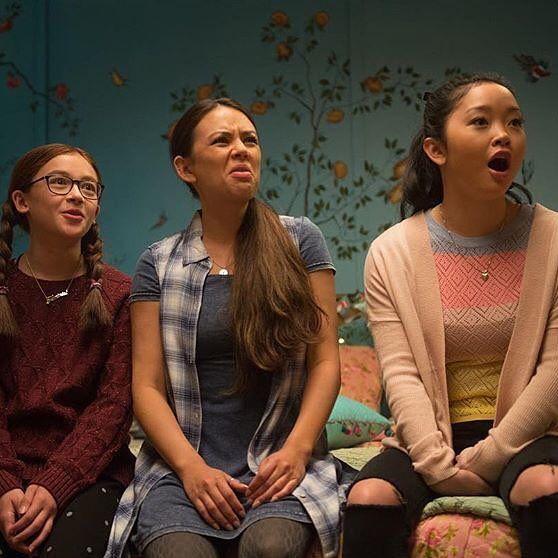tres mujeres jóvenes sentadas en una cama con gesto de sorpresa
