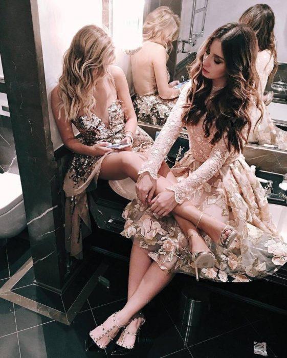 Chicas con vestidos de fiesta sentadas en el lavabo de un baño