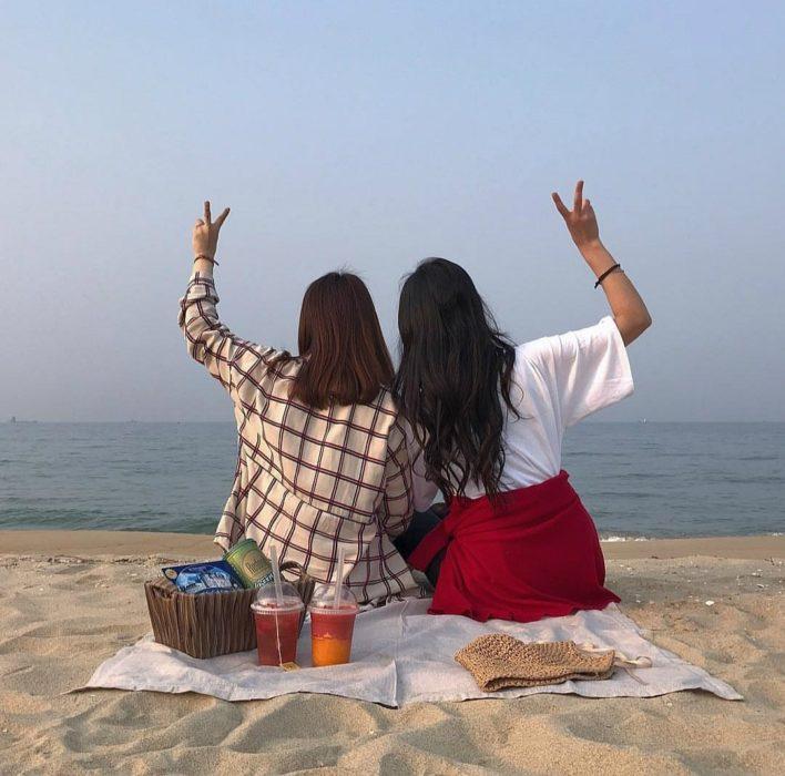 chicas sentadas en la arena haciendo un picnic