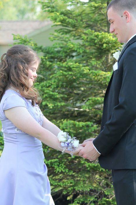Chico tomando de las manos a una chica con síndrome de Down