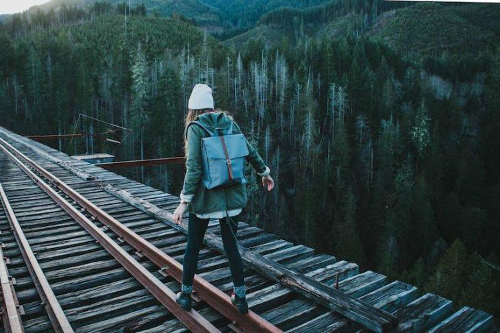 chica caminando en las vías de un tren