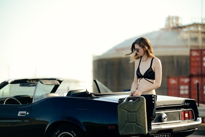 chica con una maleta recargada en un carro